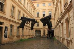 инсталляция в подворотне Праги со стреляющими пистолетами