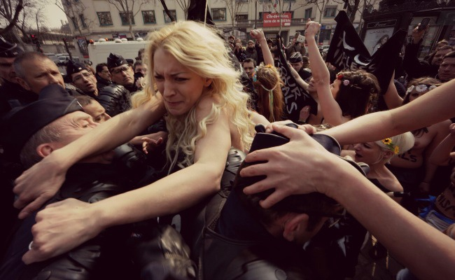 Ukrainian activist Inna Shevchenko (center) And members from The women's rights group Femen struggle with police officers during A protest In Paris April 4