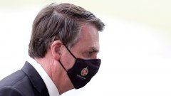 Brazilian President Jair Bolsonaro wears a mask as he leaves his official residence, Alvorada palace, in Brasilia.jpeg