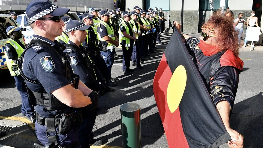 Police and a Black Lives Matter protestor are seen during a protest outside the Roma Street Magistrates Court in Brisbane.jpeg