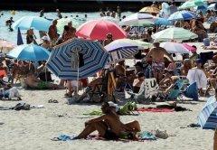 Люди наслаждаются солнечной и теплой погодой на пляже в Каннах, Франция.jpg